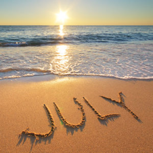 July carved in wet sand at beach